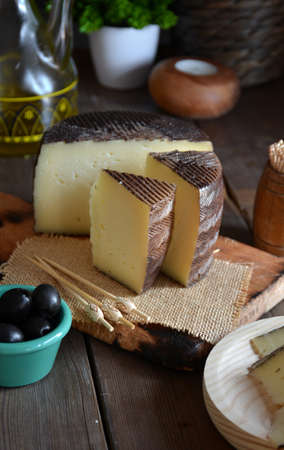 Pieces of manchego cheese cured on a wooden table accompanied by olives