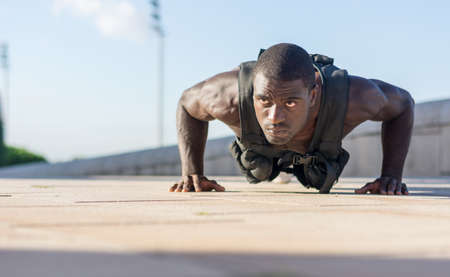 Muscular man doing push-ups with a full of weight vest
