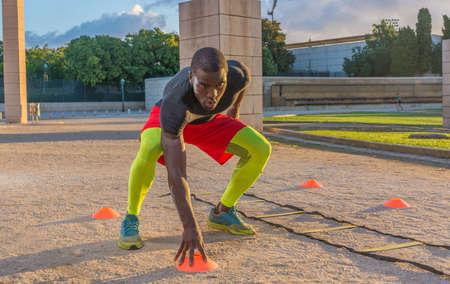 Escalera de entrenamiento muscular masculina al suelo y conos. Esto sirve para aumentar la velocidad y los reflejos. Foto de archivo - 86950326