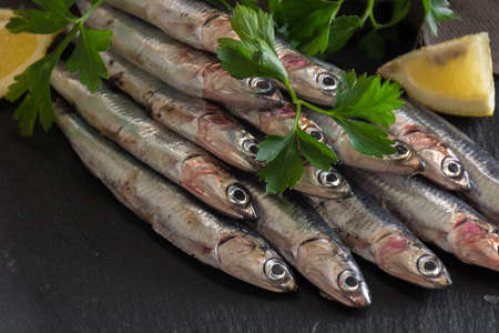 Fresh anchovies ready to Cook, accompanied by lemon, garlic and parsley Stock Photo