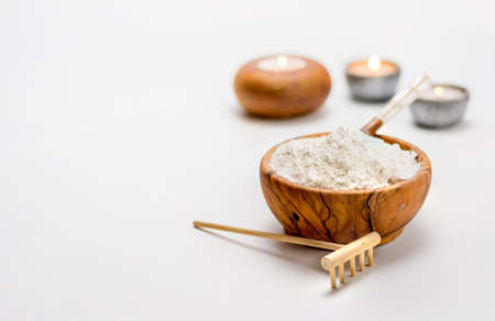 Wooden Bowl full of white clay ready to be used in treatment for the face Stock Photo