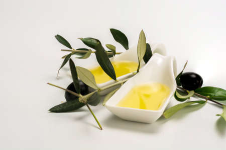 small dish full of olive oil and accompanied by some branches of a forgot with olives Stock Photo