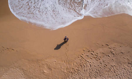 View aerial of a single beach where there is a person walking with a drone control