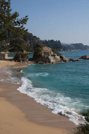 Lonely Beach on a sunny day with big waves. The place is in Spain, on the Costa Brava Stock Photo