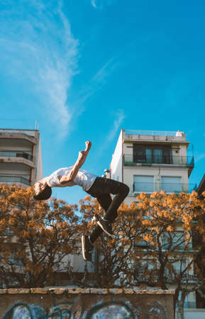 young sportsman practicing parkour, acrobatics and deadly jumps in the streets of the city