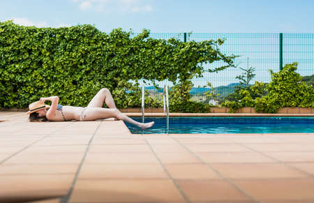 16 year old girl sunbathing peacefully in the pool of her house one summer afternoon