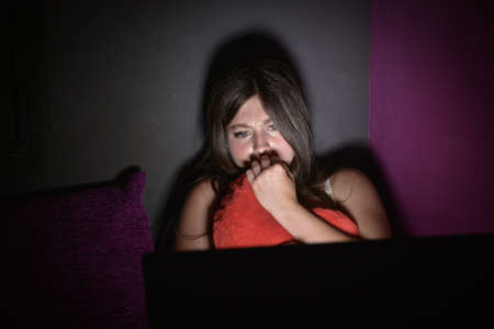 Teenage girl is afraid to watch a horror movie on her laptop.