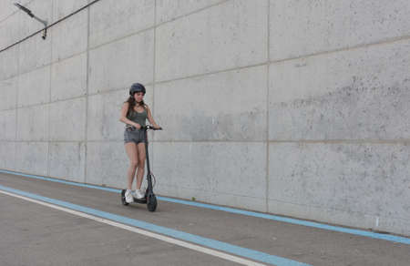 Teenage girl circulating with an electric scooter through the city