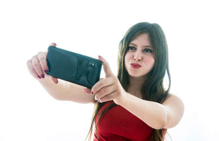 Portrait of teenage girl making a selfie with her smartphone and throwing kisses