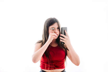 Teenage girl putting on a little makeup, seeing herself reflected on the screen of her mobile phone.
