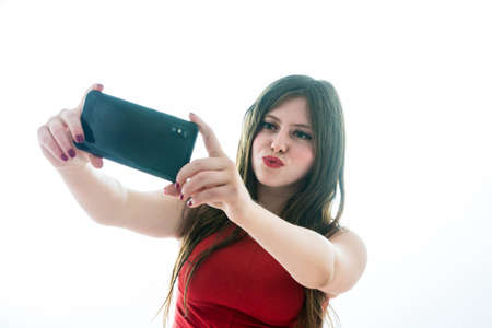 Portrait of teenage girl making a selfie with her smartphone and throwing kisses Stock fotó - 129829630