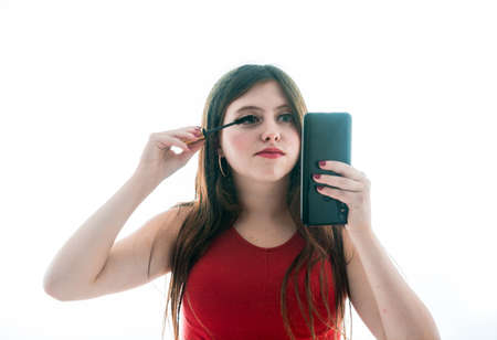 Teenage girl of 17 years quite presumed, she is arranging the eyelashes while she looks reflected in the screens of her mobile. 写真素材