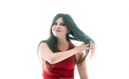 17-year-old teenage girl moving her hair freely over white background Banque d'images - 129829658