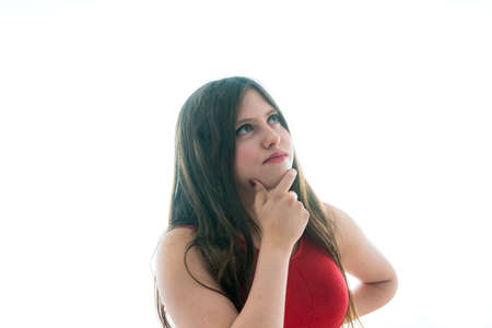 Portrait of a 17 year old adolescent girl thinking and looking upwards with a red shirt and white background.