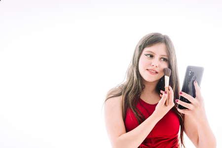 Adolescente poniéndose un poco de maquillaje, viéndose reflejada en la pantalla de su teléfono móvil. Foto de archivo