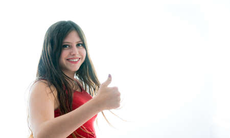 17-year-old teenage girl doing victory symbol with her hands. Photo on white background