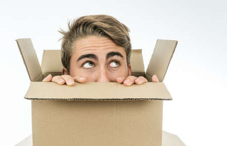 Boy with a face of surprise with his head inside a cardboard box.