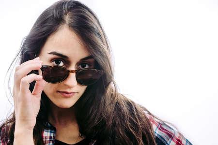 Chica con sombrero y gafas de sol haciendo posturas frente a ti.