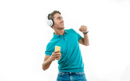 attractive man listening to music with headphones and dancing happily