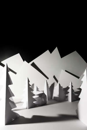 Snowy landscape of high mountain with white pines, and house in the middle of the landscape. Composition made in paper