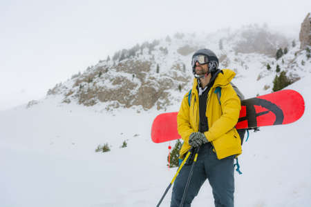 Free rider with snowshoes and snowboard on his back, contemplating the snowy landscape around him