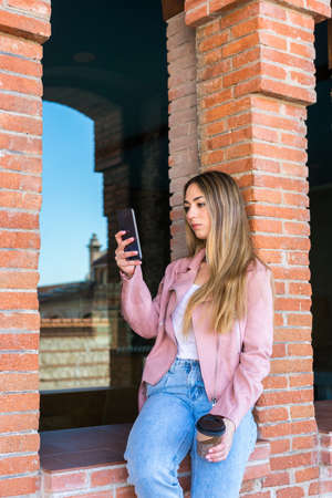 Blonde girl looking at her cell phone and taking out her selfies while waiting for her friends