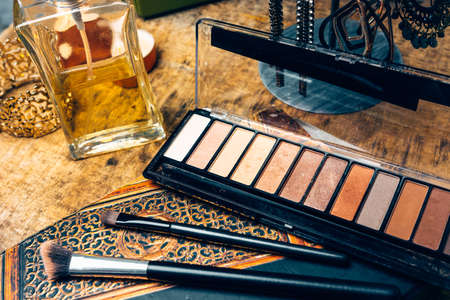 Make-up products for women on a table accompanied by different accessories
