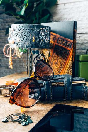 Desk full of outfit for women like sunglasses, earrings, mobile phone Standard-Bild