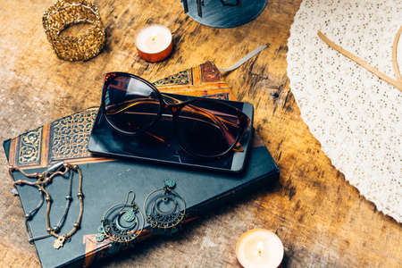 night table full of complements for the woman like her earrings, perfume, mobile phone and agenda Standard-Bild