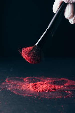 Pinceau de maquillage avec explosion de poudre violette sur fond noir