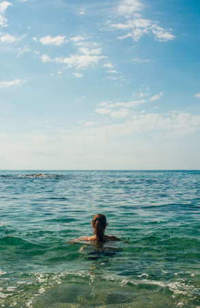 40-year-old woman enjoying a sunny summer day at the beach. Taking a refreshing swim in the sea
