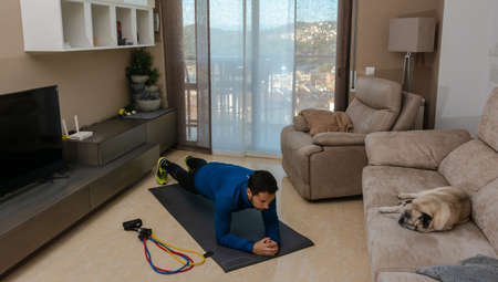 Latin man, doing a workout in his living room, does sit-ups, stretches and squats