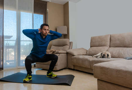Latin man, doing a workout in his living room with a rubber band while taking an online class