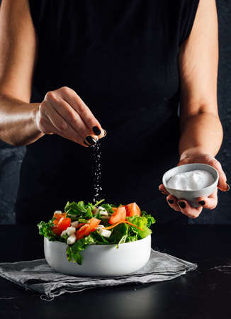 Woman preparing a salad with tomatoes, lettuce, olive oil and salt Concept of healthy diet Standard-Bild