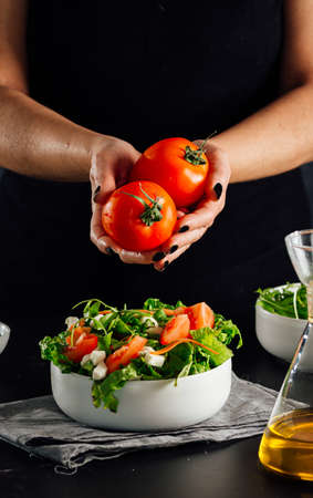 Woman holding a couple of tomatoes to add them to the salad to be eaten (Healthy and fit diet concept) Standard-Bild