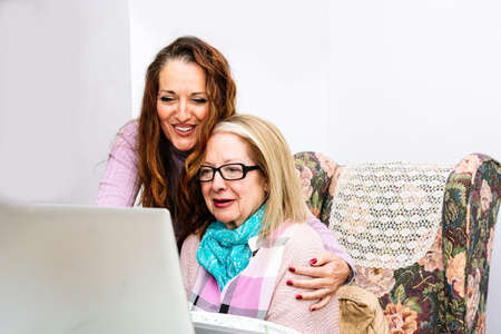 78-year-old grandmother using a laptop at home (concept of technologies for the elderly)