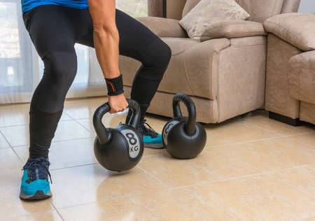 Latin man performing a cross fit workout at home with a pair of kettlebells. Standard-Bild