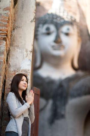 Beautiful young girl   blessing  big buddha at Srichum temple  Sukhothai - Thailand Stock Photo - 12723846