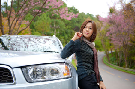 Beautiful young girl resting at side of her car at pink flower in background photo