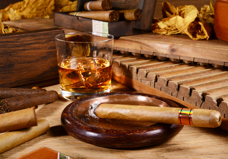 Cigars and whiskey on wooden background