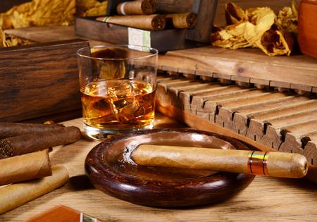 Puros y whisky sobre fondo de madera