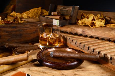 Cigarros con prensa de puros y hojas de tabaco sobre fondo de madera