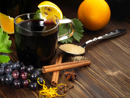 Mulled wine with cinnamon on wooden background