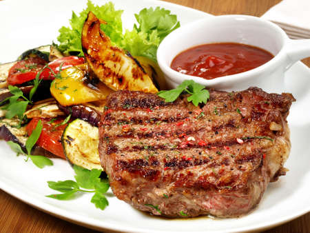 Medium Beef Steak with grilled Vegetables and Barbecue Sauce Isolated