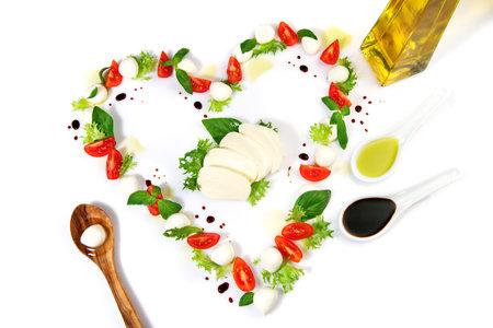 Tomato Mozzarella Heart Shape with Basil isolated on white Standard-Bild