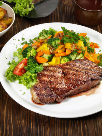 Entrecote Double with Vegetables on wooden background 版權商用圖片