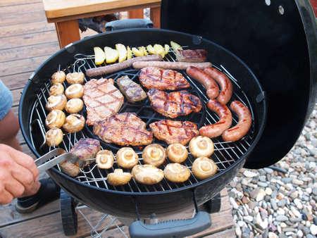 Men is grilling Meat, Sausages and Mushrooms 版權商用圖片