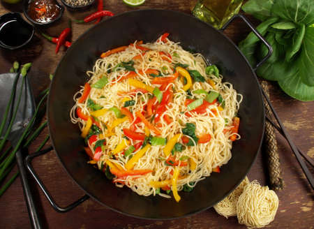Vegetarian wok with noodles on wooden background.