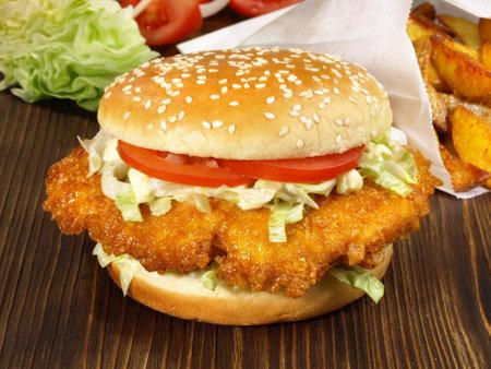 Chicken burger with tomato on wooden background. 版權商用圖片