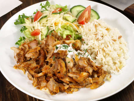 Gyros with Rice and Salad on wooden background.